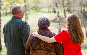 image of an older couple and a younger caregiver, all facing away from camera